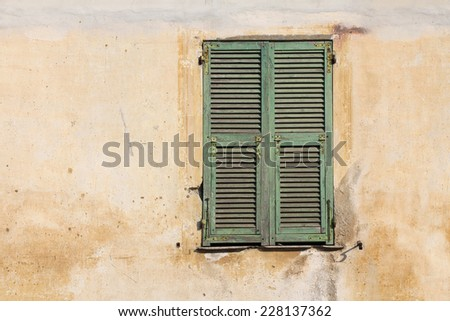 Old green wooden window on the old cracked facade - stock photo