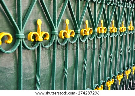 Old ,green, wrought iron fence, with yellow tips. - stock photo