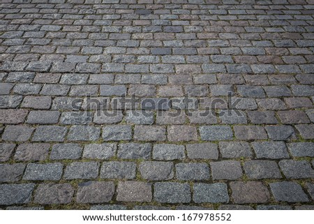 Old grey pavement in a pattern in an old medieval european town. - stock photo