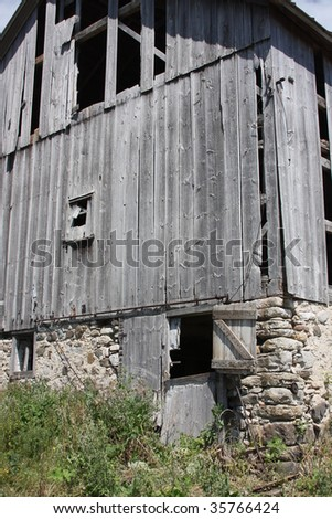 old grey wisconsin barn with stone foundation - stock photo