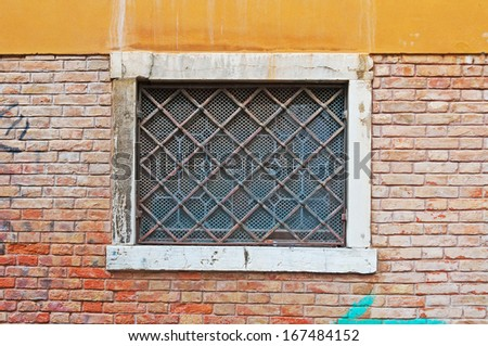 old grilled window in a brick wall in Venice, Italy