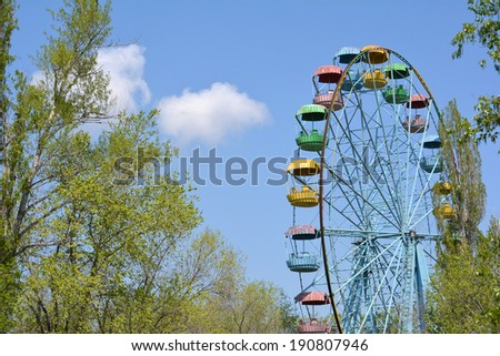 Old grunge ferris wheel in the park against blue spring sky - stock photo