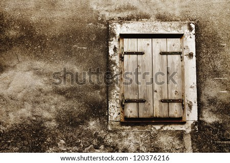 Old grunge window with closed shutters - stock photo
