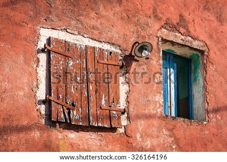 Old grunge wooden window on abandoned house - stock photo