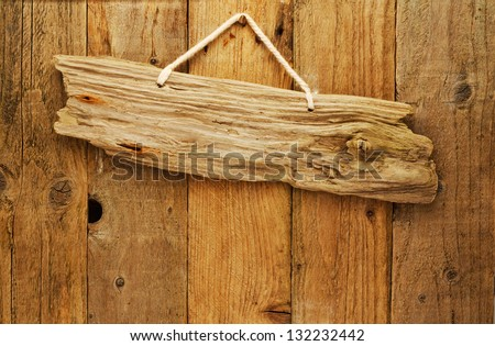 old grungy antique wooden plank of driftwood sign on string hung on aged wood door - stock photo