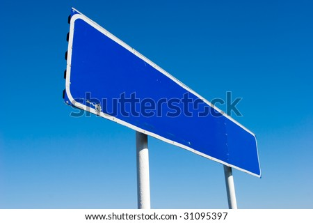 Old grungy blank signpost against blue sky