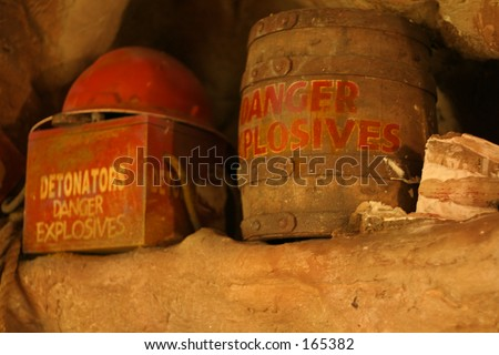 Old grungy explosives and mining helmut in a cave (shallow dof) - stock photo