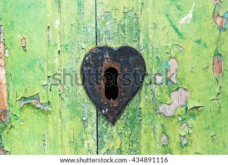 Old grungy green wooden door with peeling paint and rusted lock with a heart shaped escutcheon around the key hole