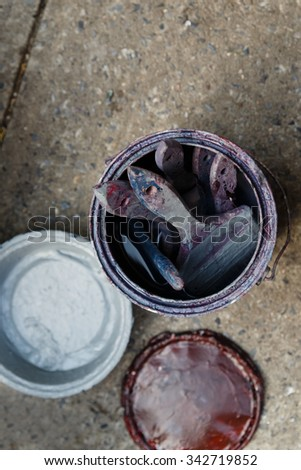 Old grungy paint cans and brushes on a sidewalk covered with red and blue paint. - stock photo