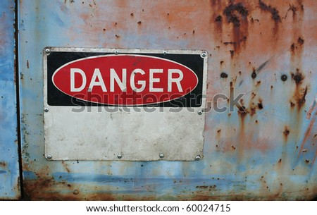 Old grungy warning sign showing danger with room for you text with rust and peeling paint. - stock photo