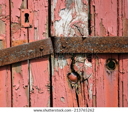 Old grungy wooden locked door with peeling paint and rusty hinge. Architectural detail. Closeup. - stock photo