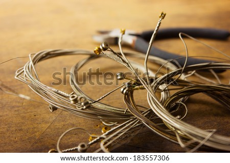 Old guitar strings, on old wooden desk. Old guitar strings, coiled and bundled. - stock photo