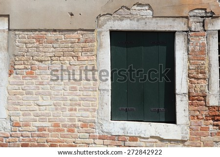 Old gungy wall with immured window - stock photo