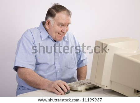 Old guy grinning at the computer - stock photo