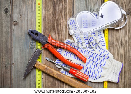 Old hammer, aged pliers, screwdriver, tape measure, gloves and safety glasses on vintage textured boards bench. still life with working tools - stock photo