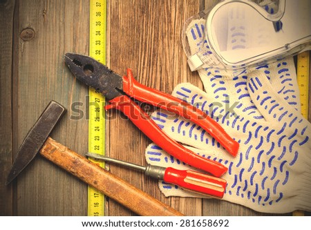 Old hammer, pliers, screwdriver, tape measure, gloves and safety glasses on old textured boards bench. still life with working tools. instagram image filter retro style - stock photo