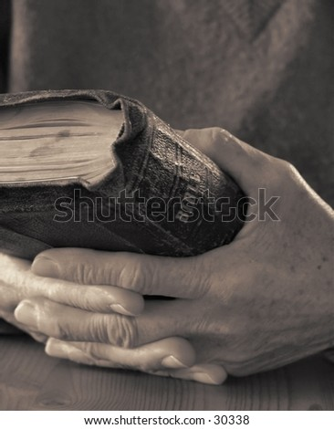 Old hands holding worn Bible - stock photo