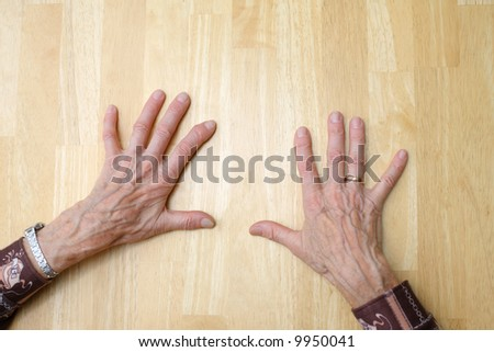 Old hands on clean table - stock photo