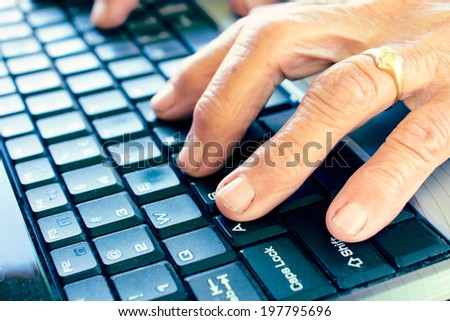Old hands typing on computer keyboard - stock photo