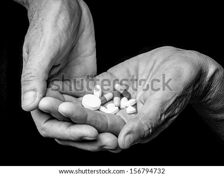 old hands with pills - stock photo