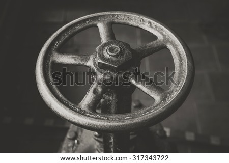 old handwheel of valve in a dark room. Black and white photo - stock photo
