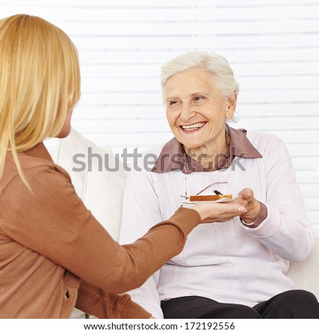 Old happy woman eating breakfast in a nursing home - stock photo
