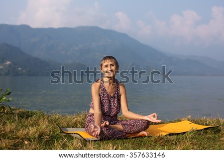 Old Happy Woman 68 years old smiling and doing yoga exercise in morning near mountain lake - stock photo