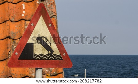 Old harbor sign warning you not to drive your classic car over the edge and plunge down into the water.  Can be used to illustrate the Wall Street Crash of 1929 since the car depicted is from that era - stock photo