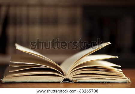 Old hardback book, open on table, with blurred bookcase behind. - stock photo