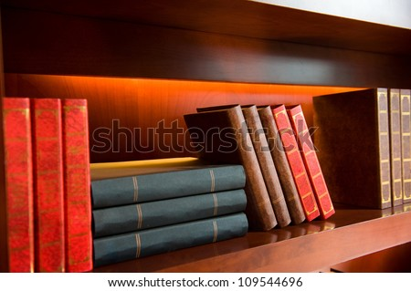 Old hardcover books on a bookshelf. - stock photo