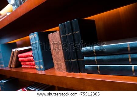 Old hardcover books on a bookshelf. - stock photo