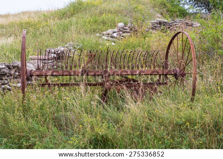 Old hay tedder on the meadow - stock photo