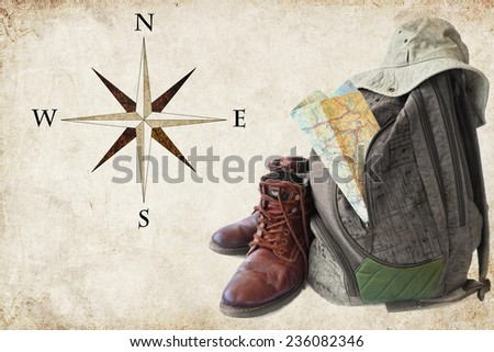 Old hiking boots, backpack, hat and the map on the paper textured Wind Rose background
