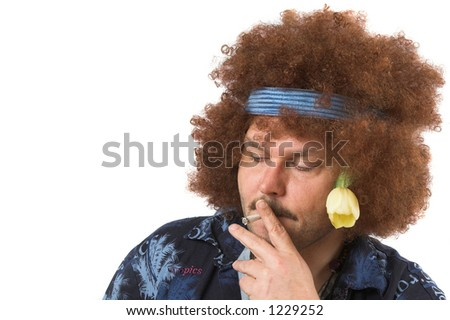 Old hippie having a smoke (text on shirt is not a brandname) - stock photo