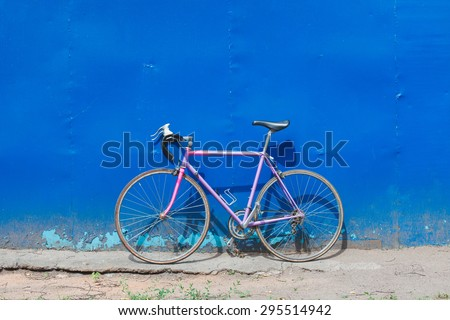 Old hipster bike stands in the blue wall outdoors in summer day. Road bikes standing on a blue wall background brutal - stock photo