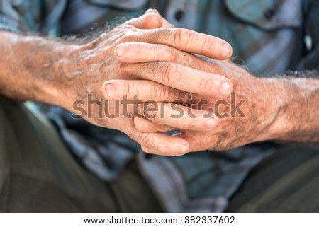 Old Hispanic man crossing his hands, revealing his missing fingers due to years working as a carpenter - stock photo