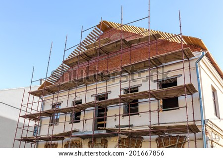Old historic building facade under reconstruction with scaffolding - stock photo