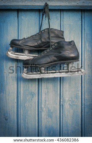 Old hockey skates hanging on a blue wooden wall - stock photo