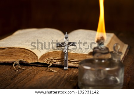 Old Holy Bible, glass gaslight and Crucifix on wooden background.