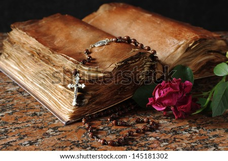 Old holy book, rose and rosary beads - stock photo