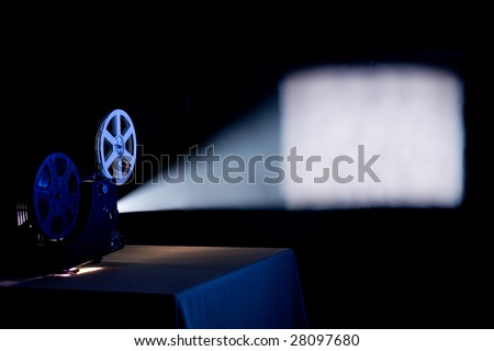 Old home film projector, running and projecting blank movie on a screen with visible  beam of light - stock photo