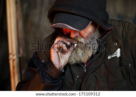 Old homeless man on the city smoking cigarette - stock photo