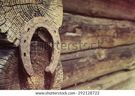 Old horseshoe hanging on the wall of the shed - stock photo