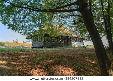 Old house of peasants in the shade of trees. Pirogovo, Ukraine - stock photo