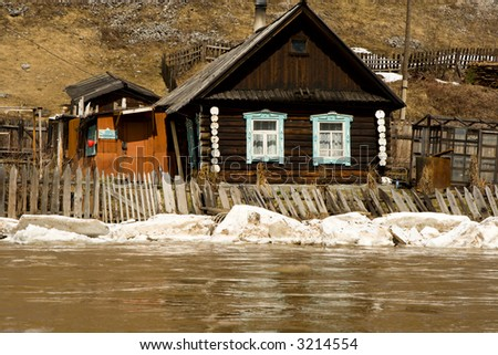 Old house on coast of the spread river - stock photo