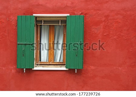 Old house red wall with green wooden window - stock photo
