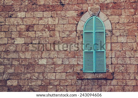 old house's wall from jerusalem stone and old blue iron shutters. retro filtered image - stock photo