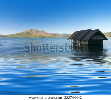old house sunk reflection in batur lake with batur mount background - stock photo