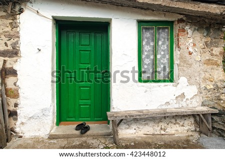 Old house wall with wooden door, window and bench - stock photo