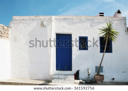 old house white wall with blue door - stock photo